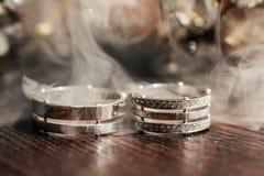 Heiratende weiße Ringe auf dem Tisch mit Rauche lizenzfreie stockbilder