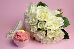Heiratender Blumenstrauß der weißen Rosen mit rosa kleinem Kuchen Stockfotos
