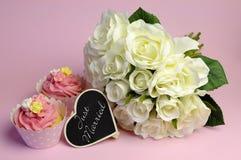 Heiratender Blumenstrauß der weißen Rosen mit rosa kleinem Kuchen und gerade verheiratetem Zeichen. Stockbild