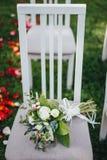 Heiratender Brautblumenstrauß mit Rosen auf dem Stuhl lizenzfreie stockbilder