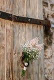 Heiratender Brautblumenstrauß von Gypsophila auf einer alten Holztür Wedd lizenzfreies stockfoto