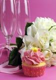 Heiratender Brautblumenstrauß von weißen Rosen auf rosa Hintergrund mit kleinem Kuchen Stockfotografie