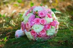 Heiratender Brautblumenstrauß auf dem grünen Gras Lizenzfreie Stockbilder