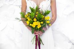 Heiratender gelber Blumenstrauß in Braut ` s übergibt weißen Hintergrund lizenzfreies stockbild