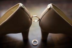 Heiratender goldener Ring zwischen den Braut ` s Schuhen auf einem dunklen Hintergrund stockfotografie