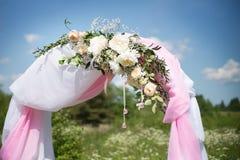 Heiratender traditioneller Bogen mit Blumendekor auf Hintergrund des blauen Himmels Stockfoto