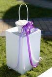 Heiratender weißer Korb verziert mit violettem Band Stockfoto