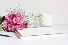 Heiratsangeredetes Foto auf Lager Stillleben mit rosa Rosen, Baby ` s Atem Gypsophila blüht, weiße Schale, Bleistift und Notizbuc Stockbild