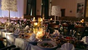 Heiratsbanketthalleninnendetails mit verziertem Gedeck am Restaurant Kerzen und weiße Blumenblattdekoration stock video footage