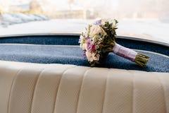 Heiratsblumenstrauß, der in einen deutschen Autoinnenraum der alten Weinlese legt stockfotografie