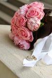 Heiratsblumenstrauß und nahe gelegene Ringe stockfoto