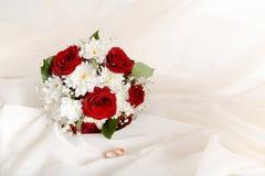 Heiratskonzeptblumenstrau? von roten Rosen und von Heiratsgoldringen auf hellem Pastellhintergrund Kopieren Sie Platz stockfoto