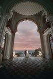 Heiratskuß unter Bogen des Palastes Stockbild