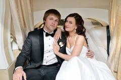 Heiratspaar umarmt in einem Auto Lizenzfreie Stockbilder