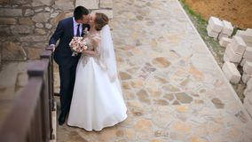 Heiratspaar zeigt ihre Gefühle auf einem Weg nahe der schönen Treppe stock video