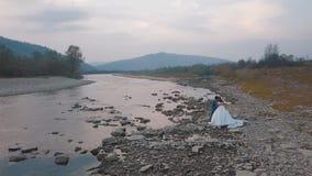 Heiratspaarstand nahe Gebirgsfluss Br?utigam und Braut Arial Ansicht lizenzfreie stockfotos