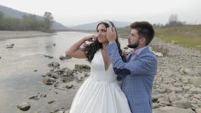 Heiratspaarstellung nahe Gebirgsfluss Bräutigam und Braut in der Liebe stock video