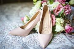 Heiratsschuhe mit Blumenstrauß auf Bett lizenzfreies stockbild