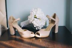 Heiratsschuhe mit künstlichem Blumenstrauß lizenzfreies stockfoto