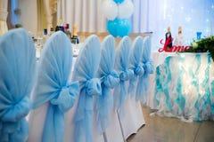Heiratsstühle mit blauen Bögen Stockfotografie