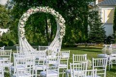 Heiratszeremoniedekoration des Sommers im Freien Schöner weißer Bogen von Niederlassungen und Blumenstrauß von weißen Rosen, von  lizenzfreies stockfoto