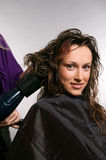 Heirdresser blow-dry hair of client Royalty Free Stock Images