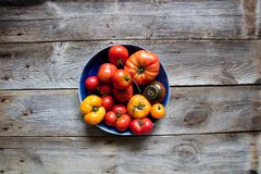 Heirloom colorful tomatoes for genuine organic mediterranean diet, copy space. Plate of different heirloom colorful tomatoes on beautiful old wooden table for Royalty Free Stock Photography