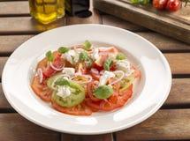 Heirloom tomato salad. Heirloom tomatoes, torn burrata, shallots, olive oil & balsamic vinegar royalty free stock photos