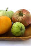 Heirloom Tomatoes. Fresh heirloom Tomatoes on wooden plate, white background Royalty Free Stock Photos