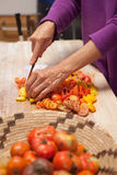 Heirloom tomatoes being cut. Woman's hands cutting heirloom tomatoes on a wooden cutting board Stock Photo