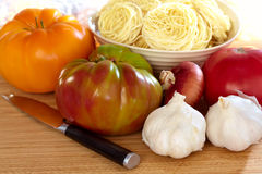 Heirloom Tomatoes, Onion, Garlic, Pasta and Knife. Heirloom Tomatoes, Onion, Garlic, Pasta and Pairing Knife On Wood Cutting Board Royalty Free Stock Images