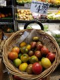 Heirloom tomatoes in round basket for sale at the market stock images