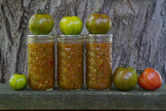 Heirloom Tomatoes and Salsa. Heirloom tomatoes and jars of homemade salsa show the before and after of home food preservation royalty free stock photos