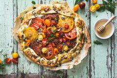 Heirloom Tomatoes Tart with Zucchini, Blue Cheese, Thyme and Honey. On Wood Background stock image