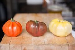 Heirloom tomatoes on a wooden cutting board. royalty free stock image