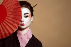 年轻heisha画象在掩藏一半她的在红色手扶的爱好者后的面孔的和服的 库存照片