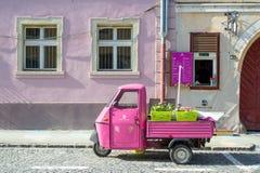 Heiss en Eis Koffie voorvenster in Sibiu, Roemenië, met een oude roze die tuk tuk vooraan wordt geparkeerd royalty-vrije stock fotografie