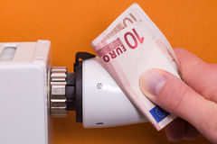 Heizkörperthermostat, Banknote und hand- Braun Lizenzfreie Stockbilder