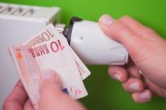 Heizkörperthermostat, Banknote und hand- Grün Lizenzfreies Stockbild
