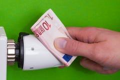 Heizkörperthermostat, Banknote und hand- Grün Stockfotos