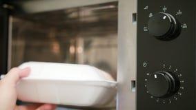 Heizung eines Behälters mit Lebensmittel in einem Mikrowellenherd stockfoto