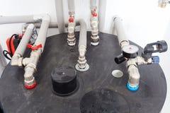 Heizungsrohrleitungen und Temperaturindikatoren im Heizraum Stockbilder