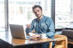 Hej dig! Ståenden av den ilskna olyckliga unga affärsmannen i jeansskjorta sitter i kafé, och ha dåligt lynne var att undervisa arkivfoto