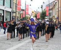 Hejaklacksledare som följs av en musikmusikband Royaltyfri Foto