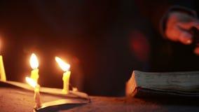 Heks die het magische ritueel houden Oude boek en kaars Halloween stock footage