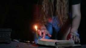 Heks die het magische ritueel houden Oude boek en kaars Halloween stock videobeelden