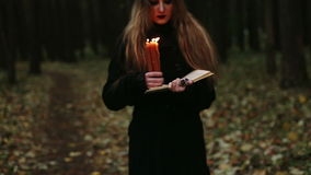 Heks met een boek en kaarsen in het bos stock footage