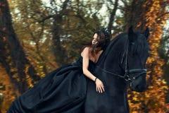 Heks van de meisjes de zwarte koningin in zwarte kleding en tiara berijdende horseback op een Friesian paard Stock Afbeeldingen