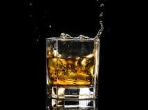 Heksagonalny szk?o whisky brandy z lodem i plu?ni?cia od spada lodu fotografia stock