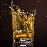 Heksagonalny szk?o whisky z lodem i plu?ni?cia od kostka lodu zaniechanego i spada obraz royalty free
